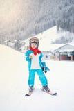 Niño pequeño adorable con la chaqueta azul y un casco, esquiando Foto de archivo libre de regalías