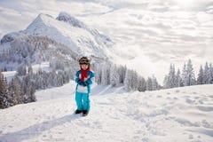 Niño pequeño adorable con la chaqueta azul y un casco, esquiando en triunfo Imagen de archivo libre de regalías