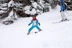Niño pequeño adorable con la chaqueta azul y un casco, esquiando en triunfo Foto de archivo libre de regalías