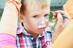 Niño pequeño adorable que consigue su cara pintada Niños pintados Imagen de archivo