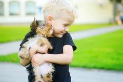 Niño pequeño adorable que juega con su perrito al aire libre Imagenes de archivo