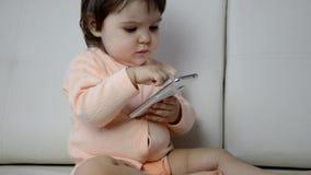 Niño pequeño adorable que se sienta en el sofá en la sala de estar y que juega con smartphone Niño que aprende cómo utilizar almacen de video