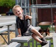 Niño pequeño adorable que se sienta en los blanqueadores en un juego de béisbol Fotografía de archivo