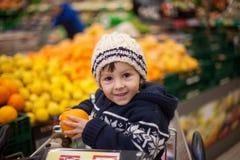 Niño pequeño adorable, sentándose en un carro de la compra Imagen de archivo