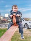 Niño pequeño alegre del  de Ð en un teetertotter fotografía de archivo libre de regalías