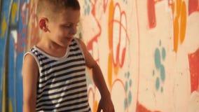 niño pequeño alegre en una camisa rayada el niño camina en zonas urbanas almacen de video