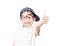 Niño pequeño alegre que detiene su pulgar Imagen de archivo