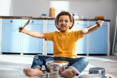 Niño pequeño alegre que finge ser un batería Imágenes de archivo libres de regalías
