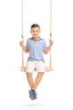 Niño pequeño alegre que se sienta en un oscilación Foto de archivo