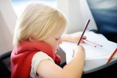 Niño pequeño alegre que se sienta por la ventana de los aviones durante el vuelo Imagenes de archivo