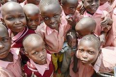 Niño pequeño apretado entre los estudiantes Fotos de archivo