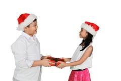Niño pequeño asiático que da presentes a su hermana Foto de archivo