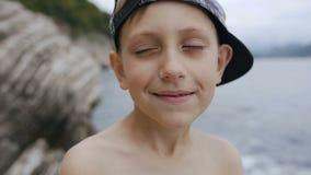 Niño pequeño atractivo con los ojos azules que miran la cámara Primer de un niño pequeño en ojos del centelleo del casquillo en l almacen de video