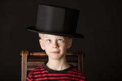 Niño pequeño carismático que lleva un sombrero de copa del tamaño de la salida Fotos de archivo