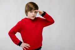 Niño pequeño caucásico confiado lindo en el suéter rojo que mira en distancia en fondo gris Imágenes de archivo libres de regalías