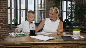Niño pequeño caucásico que viene a su abuela preciosa que trabaja con los documentos de papel en sitio de la oficina en casa medi almacen de video