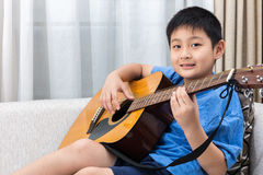 Niño pequeño chino asiático feliz que toca la guitarra en el sofá imagen de archivo