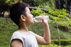 Niño pequeño chino asiático que bebe el agua mineral imagen de archivo