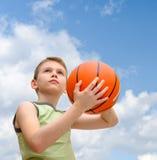 Niño pequeño con baloncesto sobre fondo del cielo azul Fotos de archivo libres de regalías