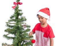 Niño pequeño con el adornamiento del árbol de navidad Imagenes de archivo