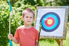 Niño pequeño con el arco grande cerca del objetivo del deporte Foto de archivo