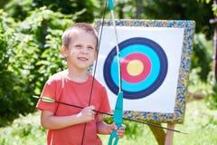 Niño pequeño con el arco grande cerca del objetivo del deporte Imagenes de archivo