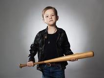 Niño pequeño con el bate de béisbol Niño divertido en la capa de cuero gamberro imagenes de archivo