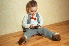 Niño pequeño con el bowtie que juega el teléfono móvil Fotografía de archivo libre de regalías