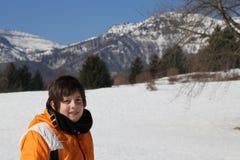 Niño pequeño con el casquillo de las lanas y la chaqueta del invierno en las montañas Foto de archivo