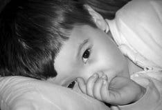 Niño pequeño con el finger en boca Fotografía de archivo