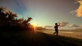 Niño pequeño con el juguete del aeroplano en una playa tropical en la puesta del sol almacen de video