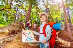 Niño pequeño con el mapa del tesoro en el juego del bosque imagen de archivo