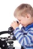 Niño pequeño con el microscopio Foto de archivo
