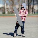 Niño pequeño con el monopatín en la calle Fotografía de archivo