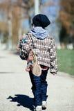 Niño pequeño con el monopatín en la calle Imágenes de archivo libres de regalías