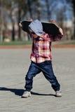 Niño pequeño con el monopatín en la calle Foto de archivo