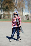 Niño pequeño con el monopatín en la calle Foto de archivo libre de regalías