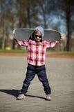 Niño pequeño con el monopatín en la calle Fotos de archivo libres de regalías