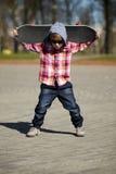 Niño pequeño con el monopatín en la calle Imagenes de archivo