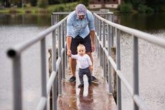 Niño pequeño con el padre que hace los primeros pasos en naturaleza Fotografía de archivo