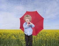 Niño pequeño con el paraguas delante de un campo de la semilla oleaginosa Fotografía de archivo libre de regalías