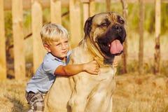 Niño pequeño con el perro grande Fotografía de archivo