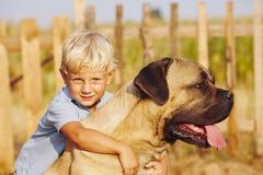 Niño pequeño con el perro grande Imágenes de archivo libres de regalías