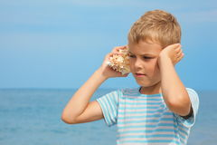 Niño pequeño con el ruido que escucha del shell del mar Foto de archivo libre de regalías