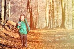 Niño pequeño con el senderismo de la mochila en bosque del otoño Imagenes de archivo