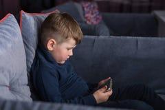 Niño pequeño con el smartphone que se sienta en el sofá Fotografía de archivo