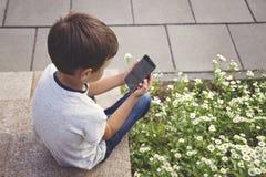 Niño pequeño con el smartphone que se sienta en las escaleras en parque de la ciudad Concepto de la tecnología, de la educación y Imágenes de archivo libres de regalías