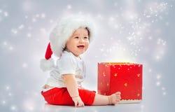 Niño pequeño con el sombrero de santa que abre una caja de regalo imagen de archivo