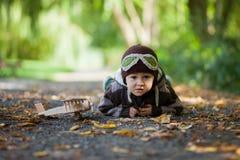 Niño pequeño con el sombrero del aviador, mintiendo en la tierra en un parque Foto de archivo