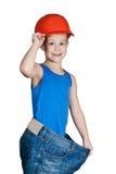 Niño pequeño con el sombrero duro y en pantalones vaqueros demasiado grandes Fotografía de archivo